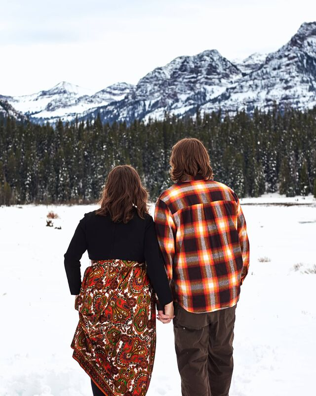 A couple walk away from the camera, hand in hand, as they look out at the mountain vistas in Hyalite Canyon near Bozeman, Montana. It is a crisp winter day, a fresh blanket of snow covering the landscape on an overcast day.