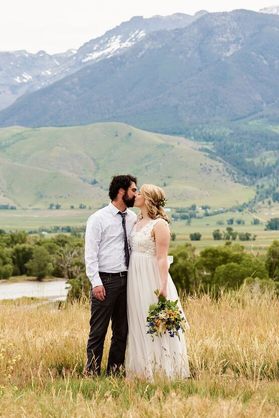 A newly wed couple stand side by side and kiss. They are surrounded by tall grass above a river with towering mountains in the distance behind them.