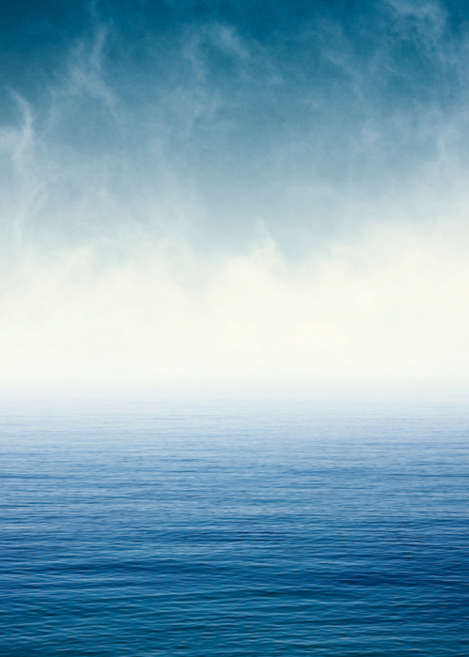 A fog appears and obstructs the view looking out onto a blue ocean horizon.