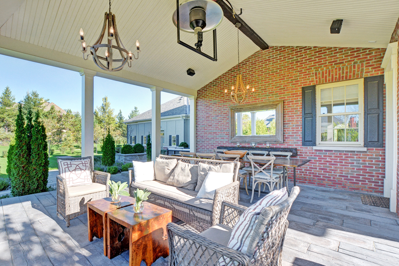 spacious covered porch with dining table and soft seating, painted vaulted wood ceiling and wood chandlers