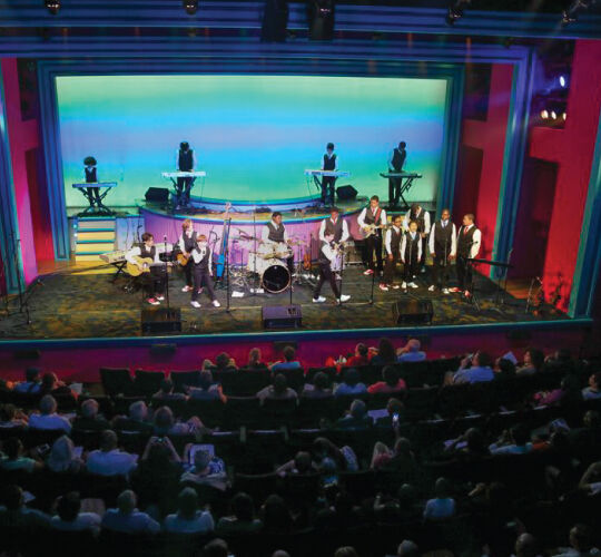 Band on stage and full audience at New World Stages