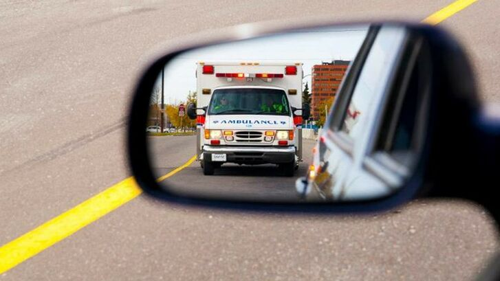 The audience for the word ambulance isn't people standing in front of it.  It's drivers on the road who are looking at their rearview mirrors to see what's behind them.