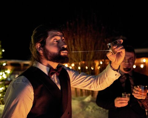The groom expresses surprise with wide eyes as he bites down and pulls the freshly made s'mores away from him. A thin trail of oozy marshmallow extends between him and the s'mores at an arm's length. The glow of firelight illuminates the scene.