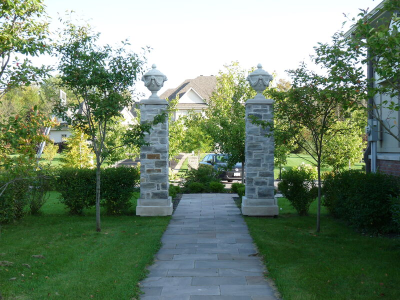 tree lined natural stone side walkway flanked by two large pillars leading to the back yard of a Georgian style estate home