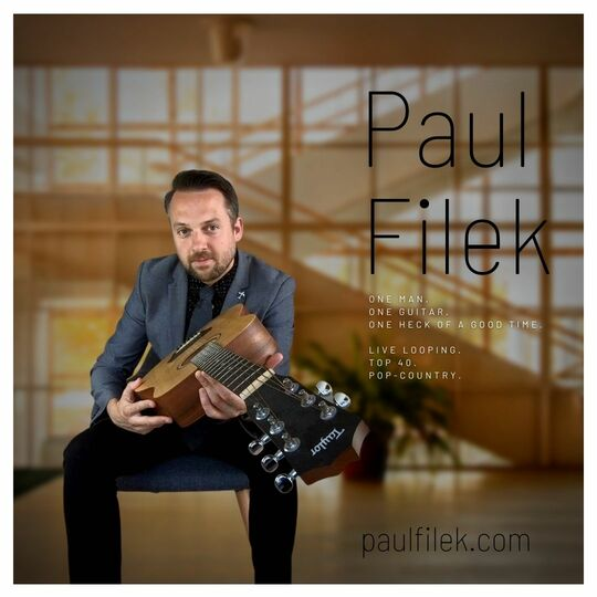 """Promotional Photo of Paul Filek sitting on a chair with his guitar in a large room with big windows and a large staircase. The poster reads  """"One Man Band, One Man, One Guitar, One Heck of a Good time"""""""