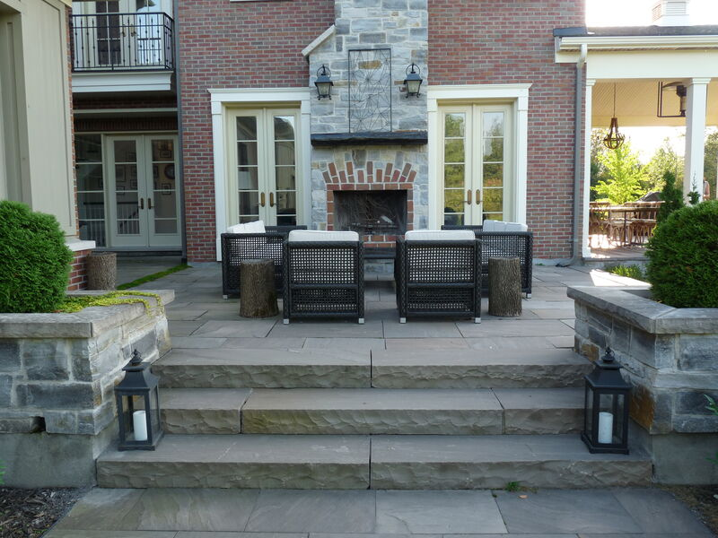 large estate back yard property with natural stone steps flanked by raised planters leading to a raised wet laid natural stone patio with outdoor wood firepace