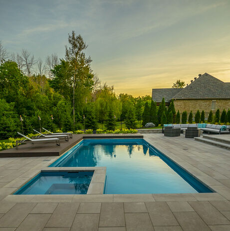 serine residential backyard landscape with a pool and interlock patio with Azek wood sunning deck with sun loungers