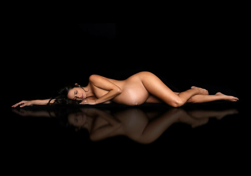 implied nude maternity portrait with mirror image in  studio