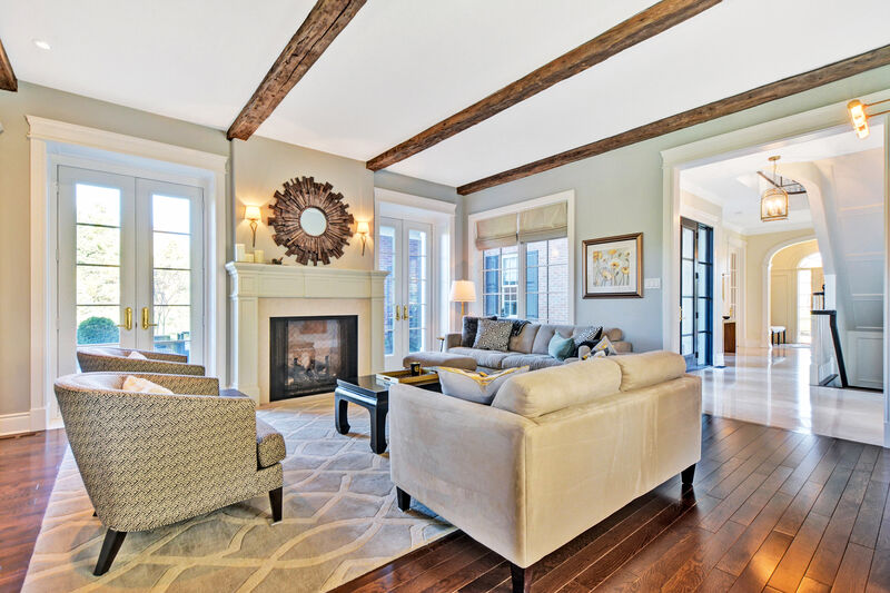 family room design with custom fireplace mantel, rustic wood beam on ceiling, dark hardwood floor and comfortable soft seating