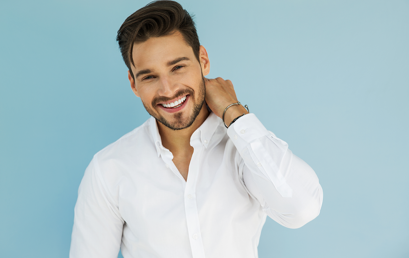 Man in white shirt smiling.