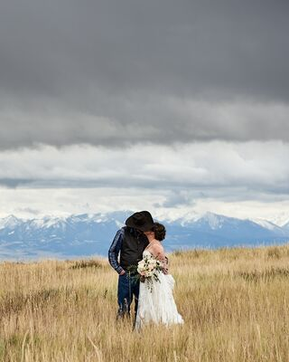 A newly wed couple lean in for a kiss. They stand in a wheat field under stormy, moody skies with the Crazy Mountains of Montana in the background.