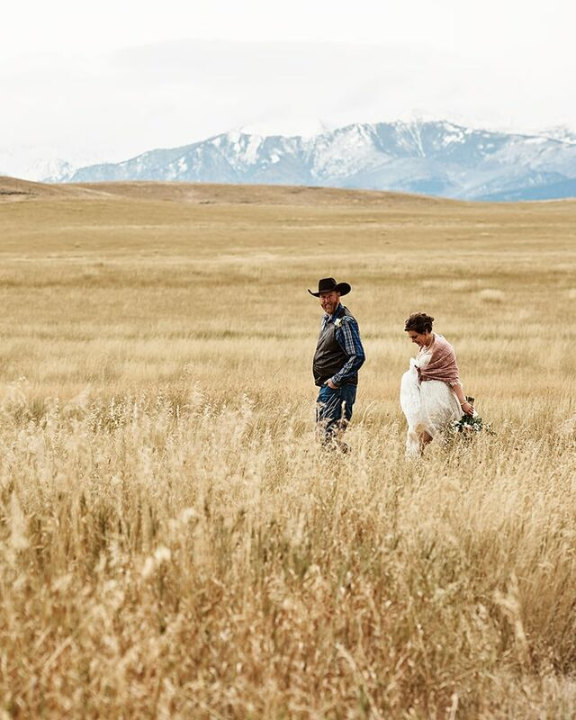 A newly wed couple walk side by side through a field of wheat near the Absaroka Mountains in Montana. The mountain range can be seen looming in the distance.