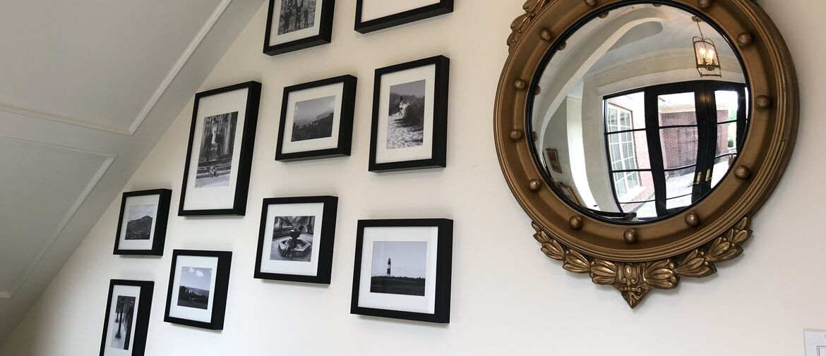 gallery wall with simple black framed black and white photos arranged on wall beside ornate gold mirror