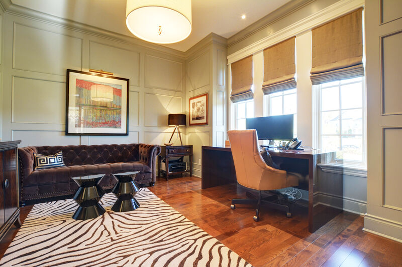 modern home office with soft seating, graphic zebra print rug and custom wall paneling