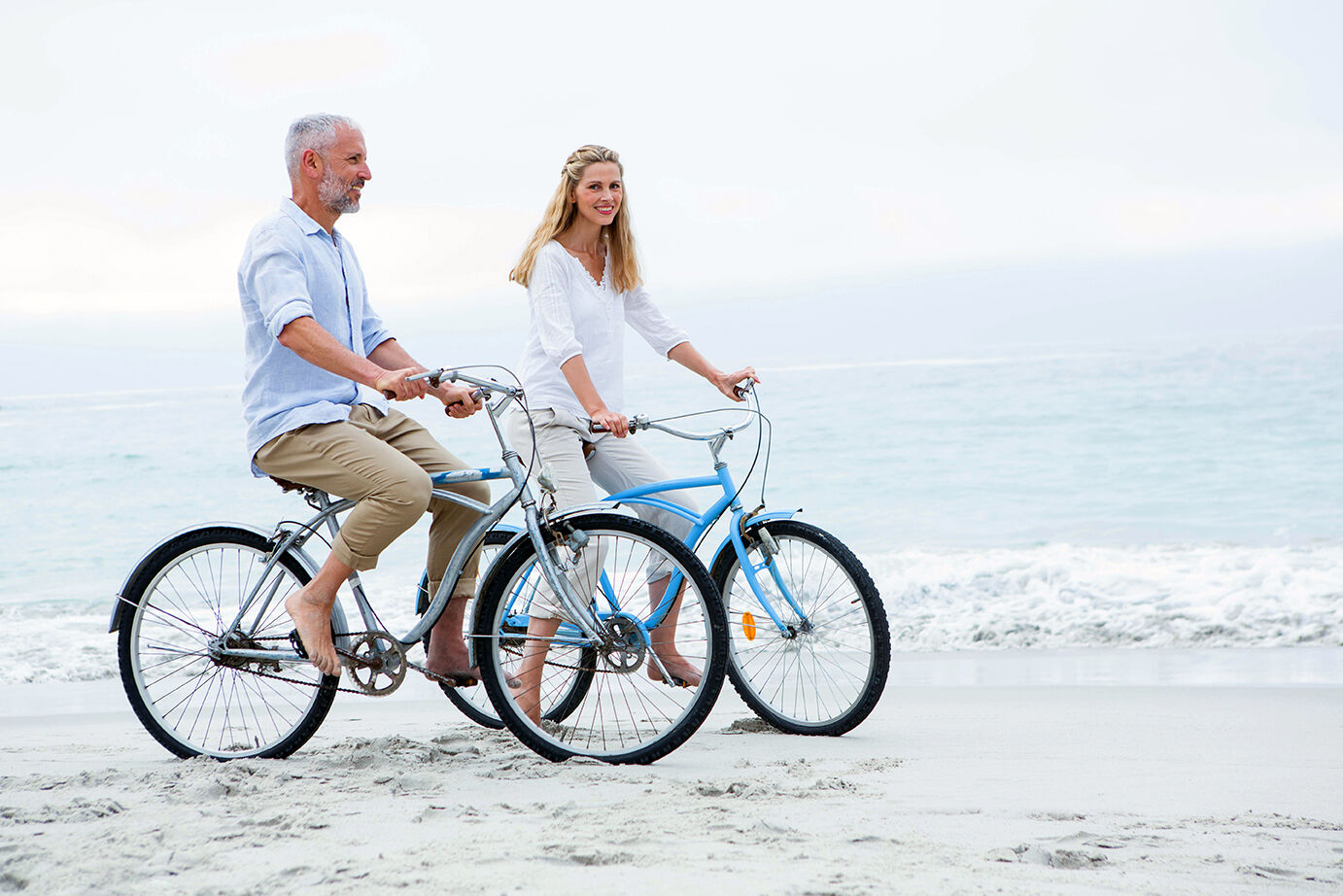 Older couple bicycling on the beach next to water.