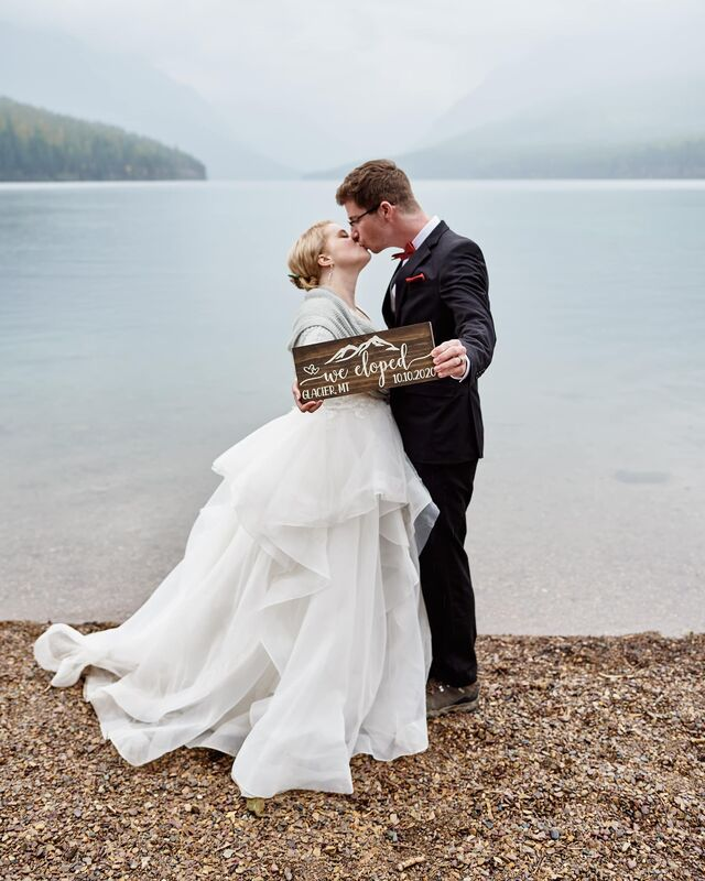 "A newly wed couple kiss as they hold out a wooden sign that reads, ""We Eloped, Glacier MT, 10.10.2020"". They stand at the edge of a lake on an overcast day, the blue and green mountains are hazy in the background."