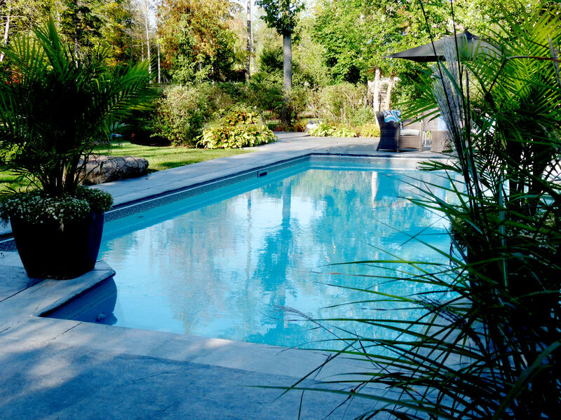 poured concrete pool patio surrounding modern rectangular pool