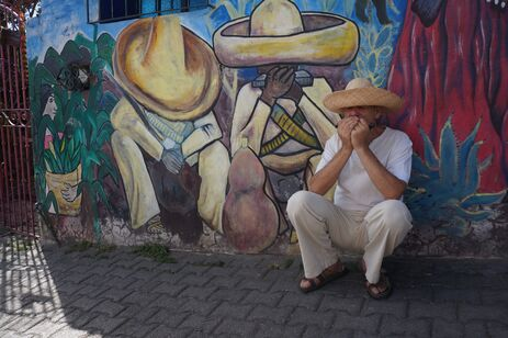 Author plays harmonica squatting in front of  a mural of musicians dressed similarly: large sombrero, white baggy clothes, sandals.