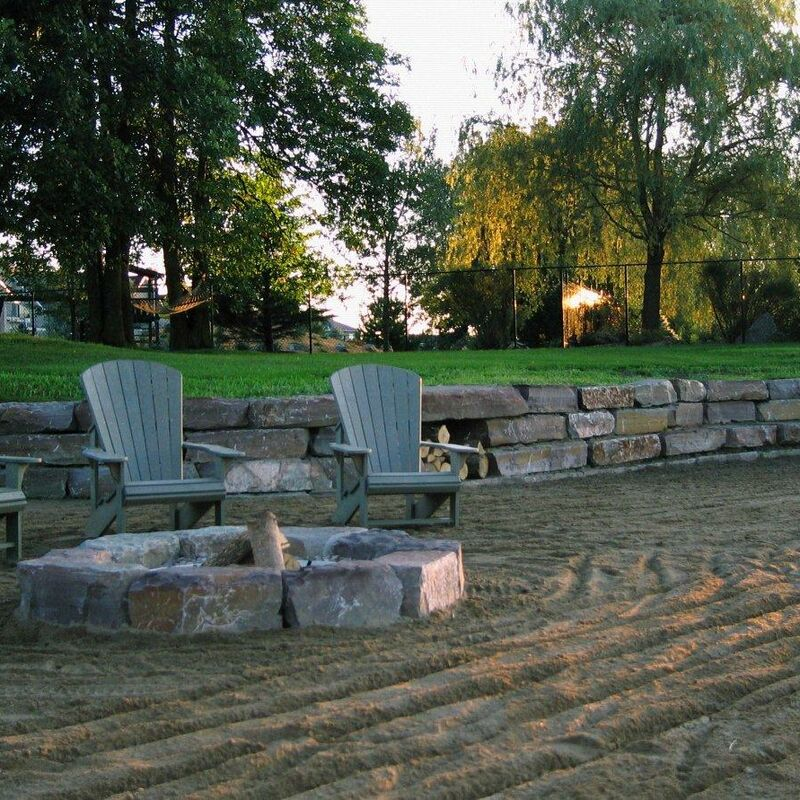 Three adirondack chairs facing a fire pit in front of a retaining wall