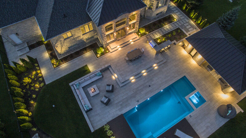 resort like residential backyard landscape design at night with a pool, hot tub, interlock patio,  wood sunning deck with sun loungers, and landscape lighting