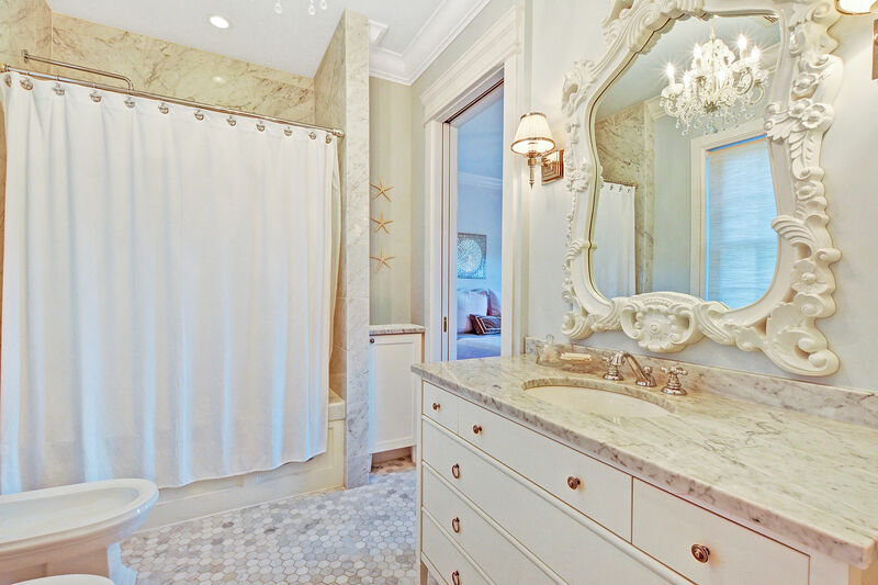 elegant bathroom with ornate mirror and crystal chandelier