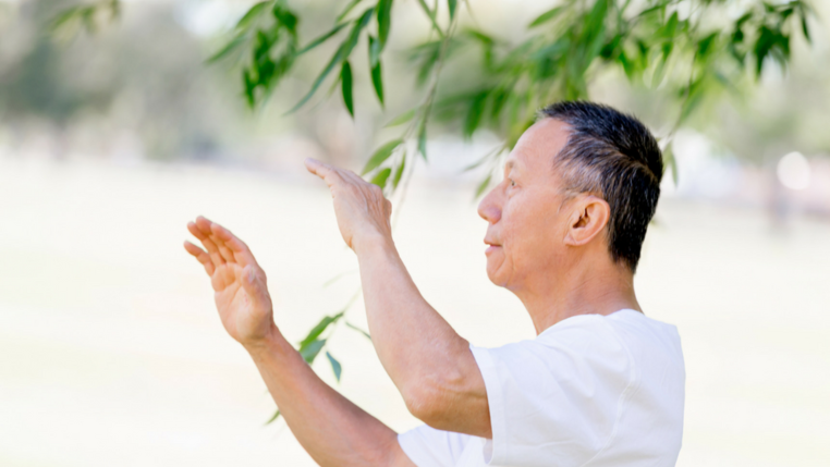 A man is pictured doing Qigong outside underneath a tree.