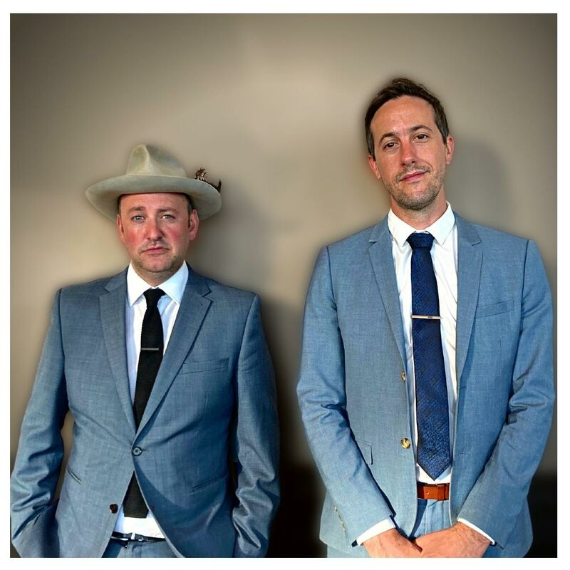 Phil Bell and Sam Cartwright both in blue suits facing the camera. Neither are smiling, both have devilish smirks on their faces