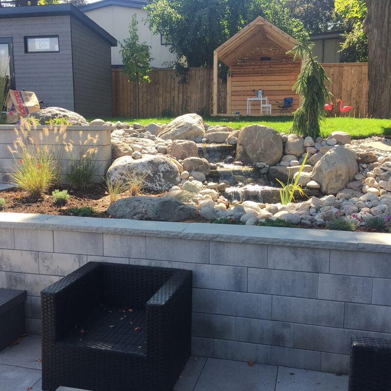 Outdoor rock garden with water feature on a retaining wall