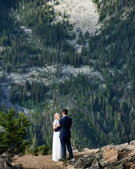 A couple embraces and laughs happy tears during their ten year vow renewal on a cliffside in the Bitterroot mountain range of southwest Montana.