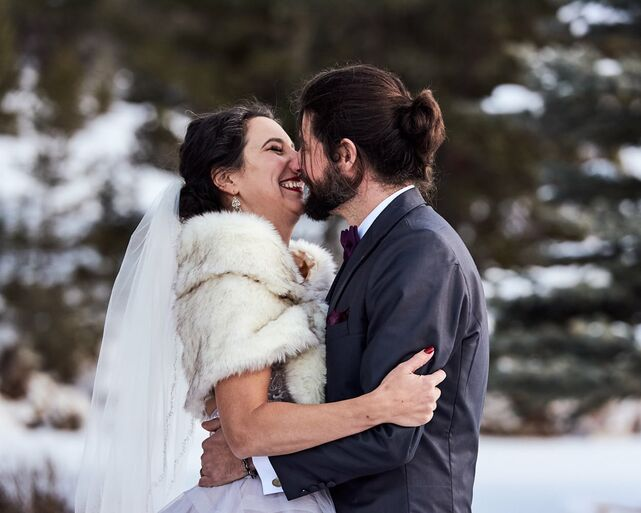 "A happy couple shares their first kiss after saying ""I do"" in an intimate, outdoor wedding in the Gallatin Valley outside of Big Sky, Montana. The bride joyfully smiles while they pull each other close."