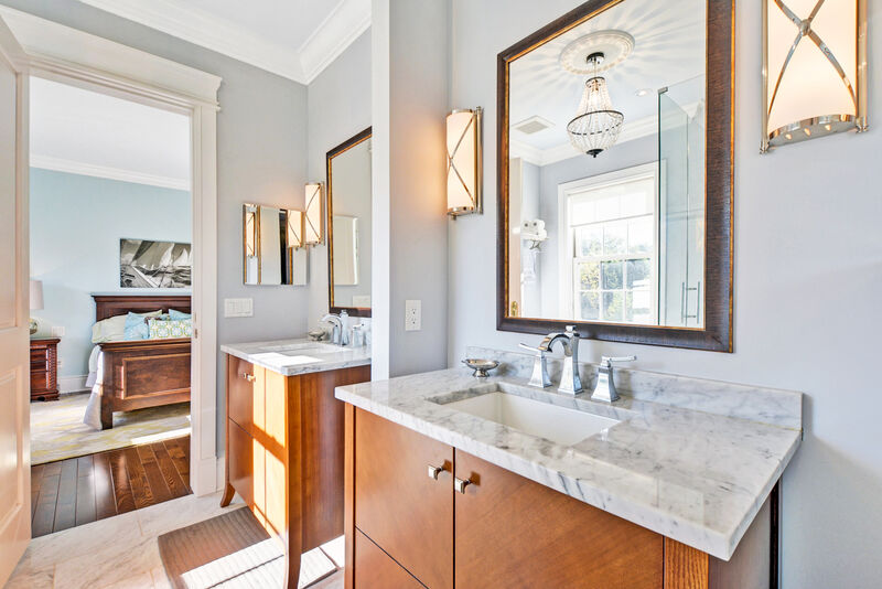 Jack and Jill bathroom with two single vanities and wall sconces flanking mirrors