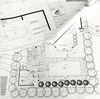paper copy of printed autoCAD interior design and landscape design plans spread out on a desk