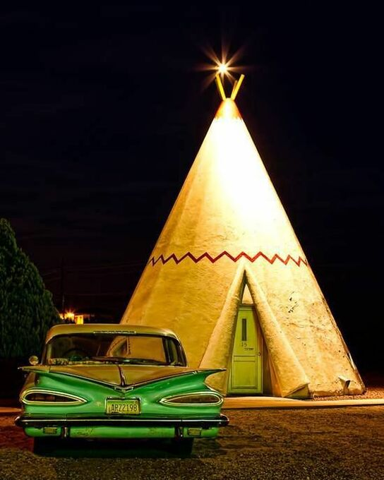 A shot of a mid-century wigwam theme motel with a classic car outside