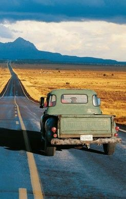 This is a pic of a pickup truck on a typical American west highway through a desert region