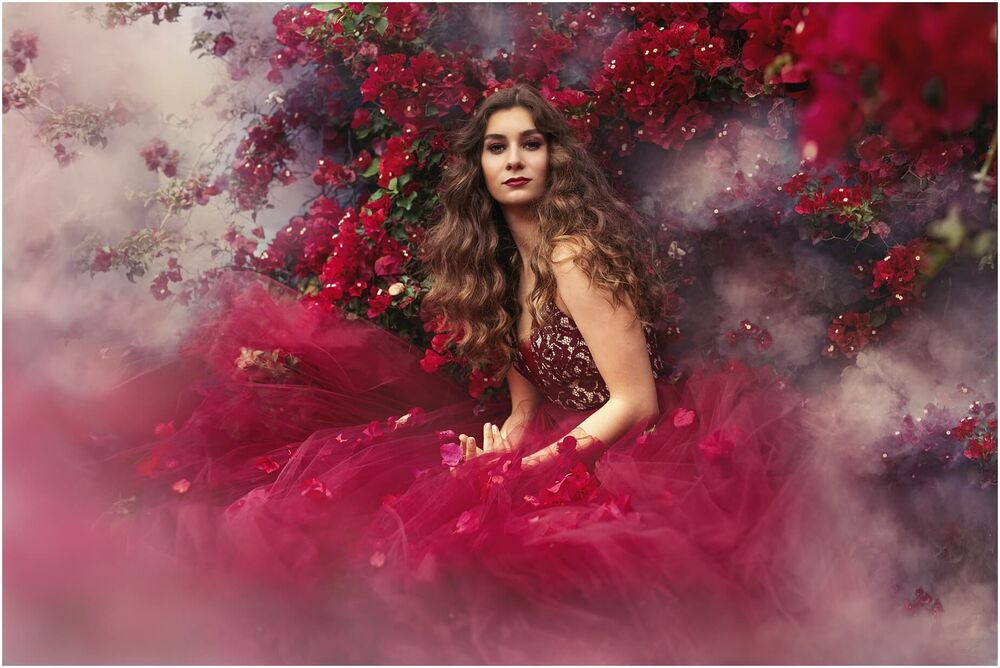 portrait of a girl surrounded by color smoke and burgundy red flowers in wine colored dress and makeup