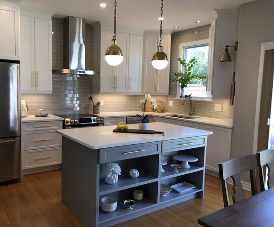 kitchen with white cabinets and a light taupe island with white quartz counters and brass fixtures