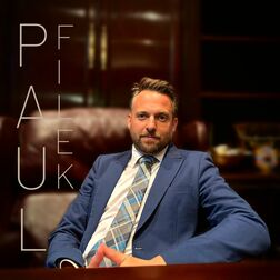 Paul Filek sitting in a brown leather chair looking at the camear in a blue suit with a white shirt and blue tie. Paul Filek is also written in text along the left side of the photo