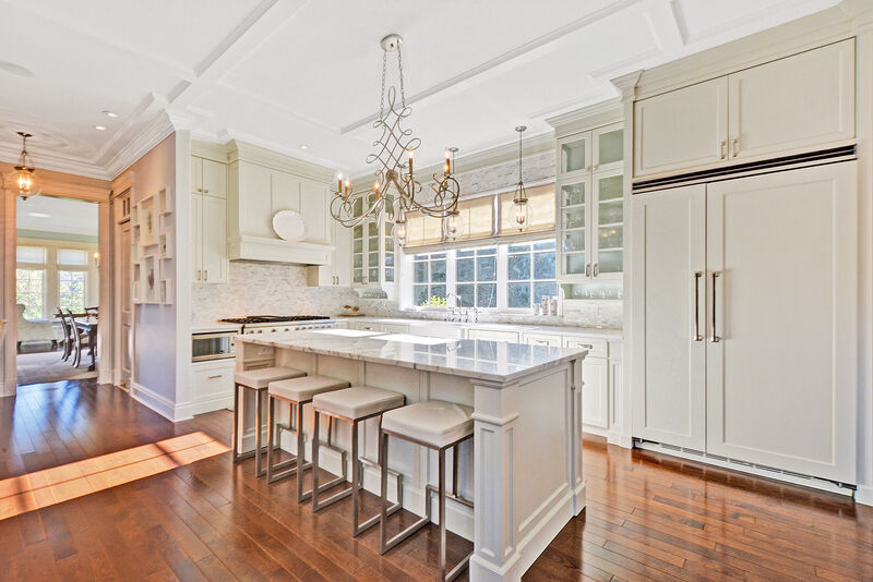 large white painted kitchen with beehive pendants, quartz counter tops, marble island and paneled appliances