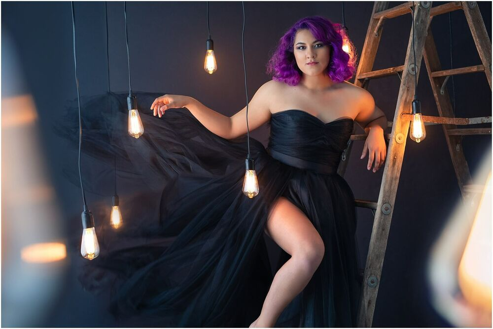 fashion portrait of girl with purple hair in black tulle gown surrounded by vintage lightbulbs