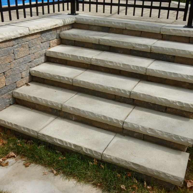 Custom built stone steps leading to a backyard swimming pool