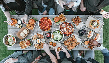 Friday Fellowship image - Group eating around picnic table