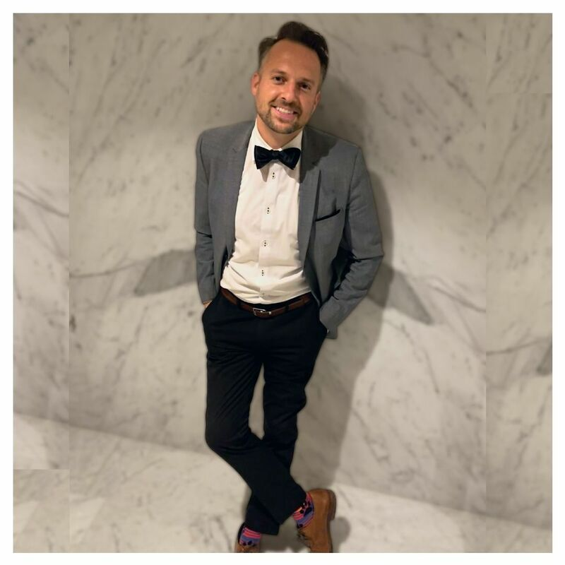 Paul Filek standing against a Marble wall inside the fairmont pacific rim lobby lounge. Paul is wearing black pants, white shirt, black bow tie, grey sports coat, brown shoes and bright multicolored socks with dog paw prints