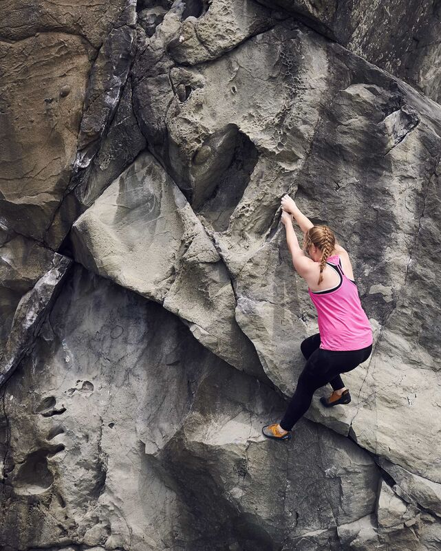Jesslyn Marie works her way up the rocky face of a bouldering problem at Moonstone Beach in California.