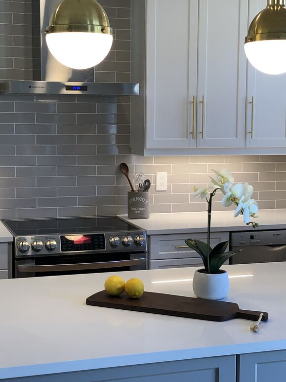 Medium sized kitchen renovation with two island pendants, a modern hood fan,  and taupe subway tile backslash