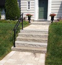 Stone steps with a single black metal railing