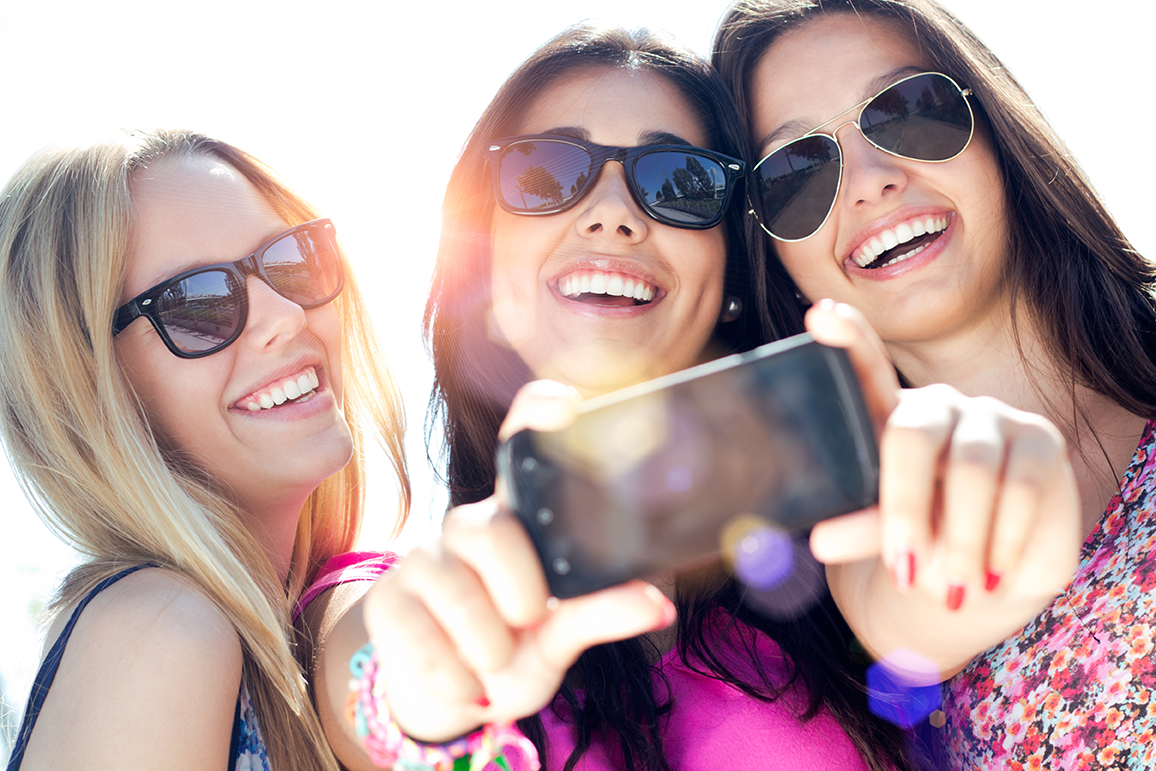 Three smiling woman taking selfies.